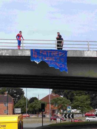 Martin Cuff, dressed as Spider-Man as part of a 'Fathers 4 Justice' protest, speaks with police officers on the flyover of the A338 Wessex Way on September 1, 2013